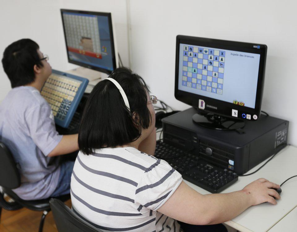 Imagem de Telecentro paulistano. Nela, usuário está utilizando um equipamento adaptado para acessibilidade por público com deficiência, enquanto usuária ao lado utiliza outro computador.