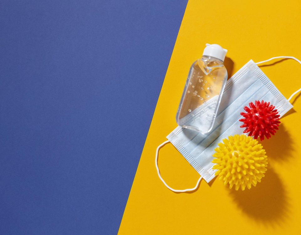 Para cego ver: Imagem traz álcool gel máscara e bolinhas em formato de coronavírus laranja e vermelha em fundo azul e laranja. (Crédito: Freepik.com)