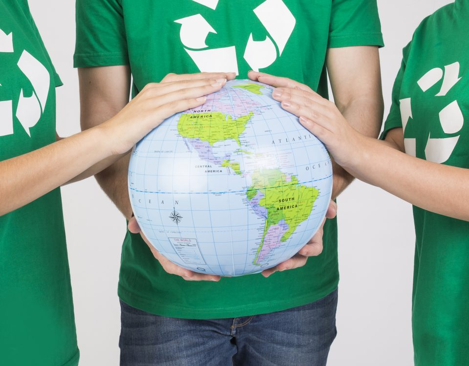 [Pra cego ver] Pessoas com camisetas verdes e com símbolo da reciclagem em destaque seguram o globo