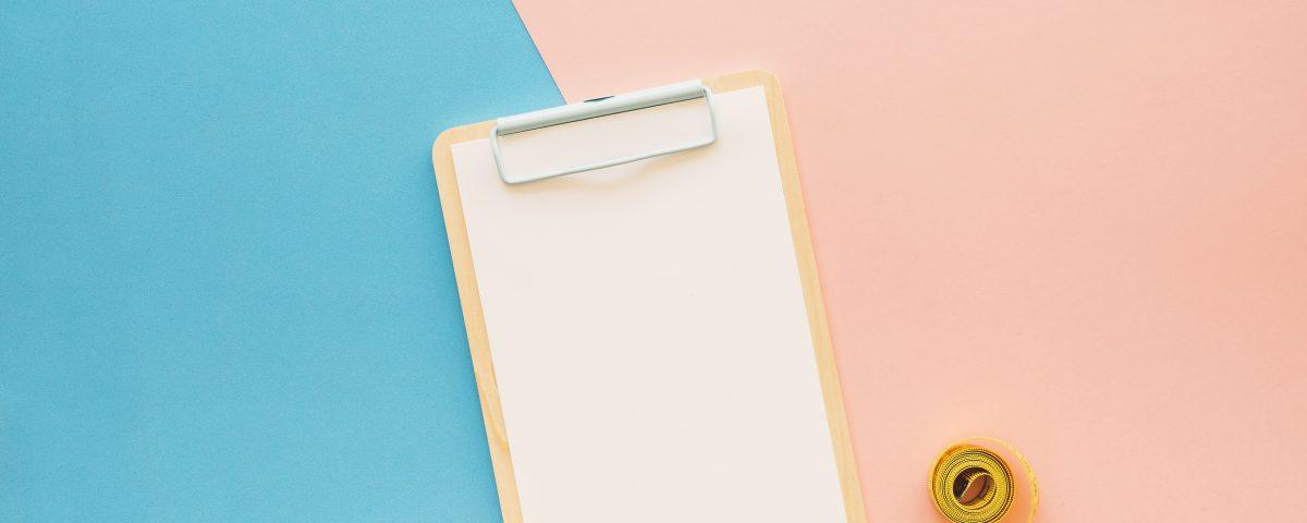 [Pra cego ver] Prancheta e fita métrica sobre fundo azul-piscina e rosa