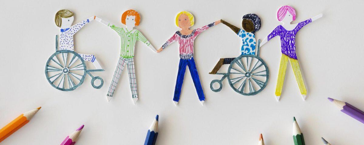 [Para cego ver] Imagem traz desenho multicolorido de pessoas de mãos dadas numa folha de papel. Duas dessas pessoas são cadeirantes. Há vários lápis de cor sobre o papel.
