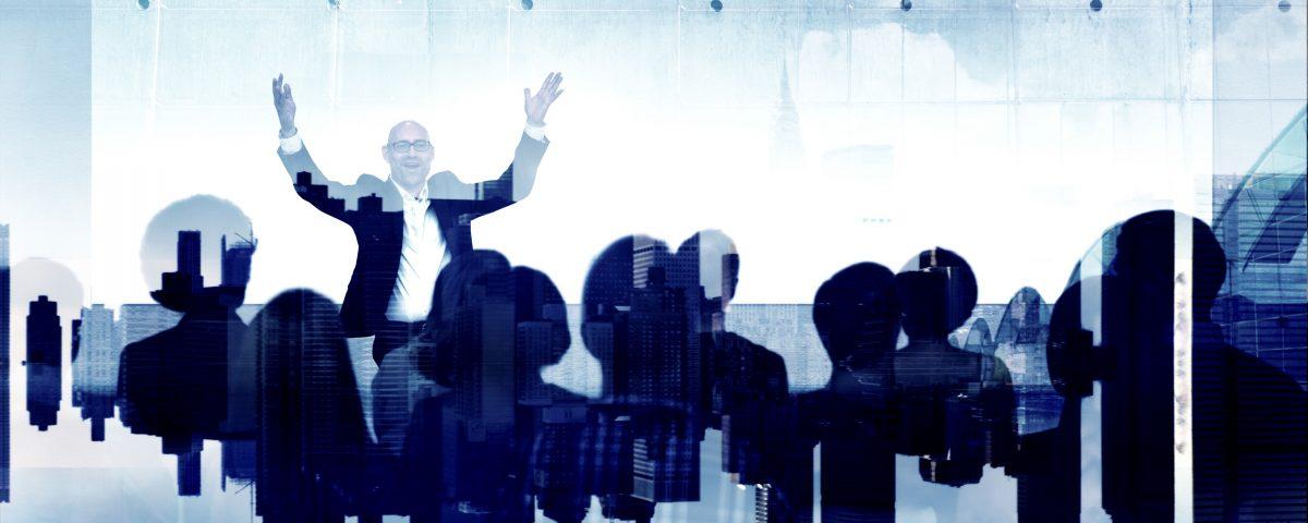 [Pra cego ver] Montagem sobre foto de seminário traz transparências em tons azuis e elementos tecnológicos sobre a imagem. De frente para o leitor, ao fundo, um palestrante acena com mãos e braços para o público à sua frente. Plateia está de costas para o leitor e em primeiro plano na imagem.