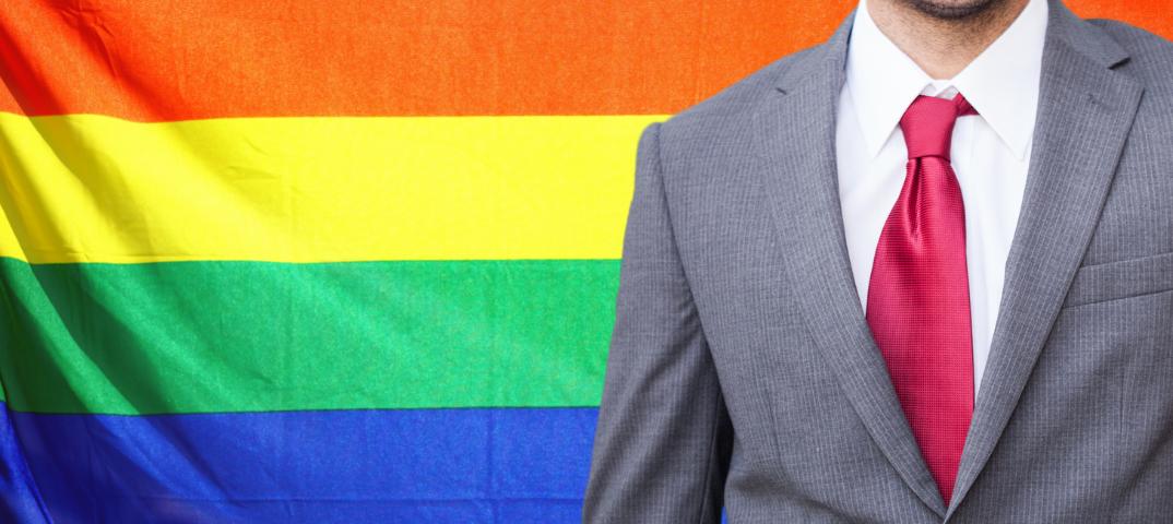 Pra cego ver: Imagem traz bandeira do movimento LGBTQIA+ ao fundo e executivo em meio corpo, à frente, mostrando parcialmente o rosto.