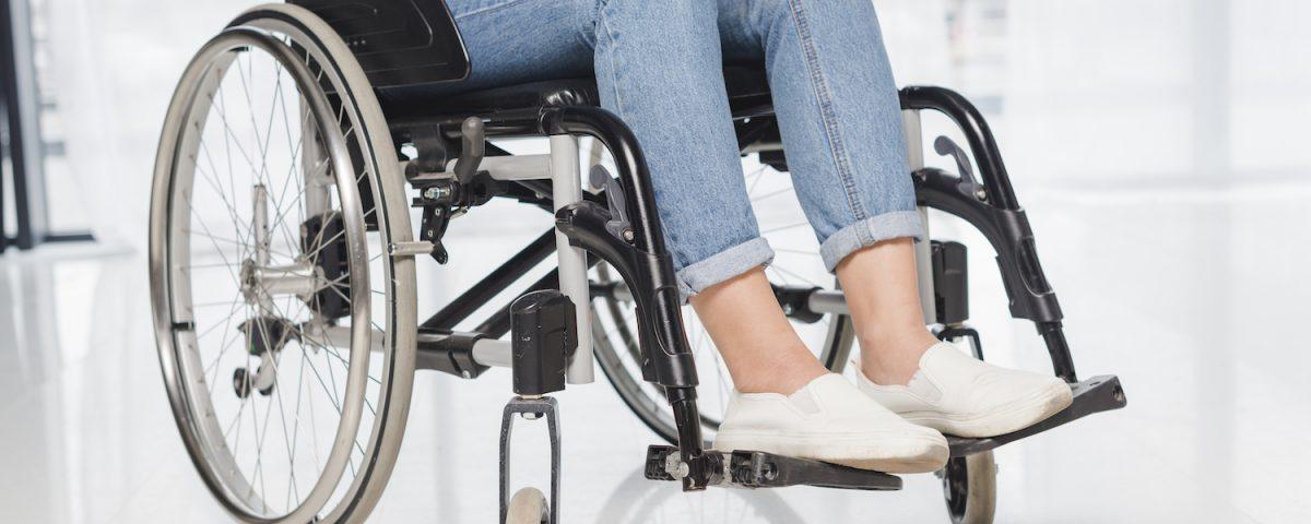 [Pra cego ver] Imagem traz recorte de foto mostrando pessoa com deficiência em uma cadeira de rodas, usando um notebook apoiado sobre as pernas. Destaque está no colo e membros inferiores da pessoa, além das rodas da cadeira.